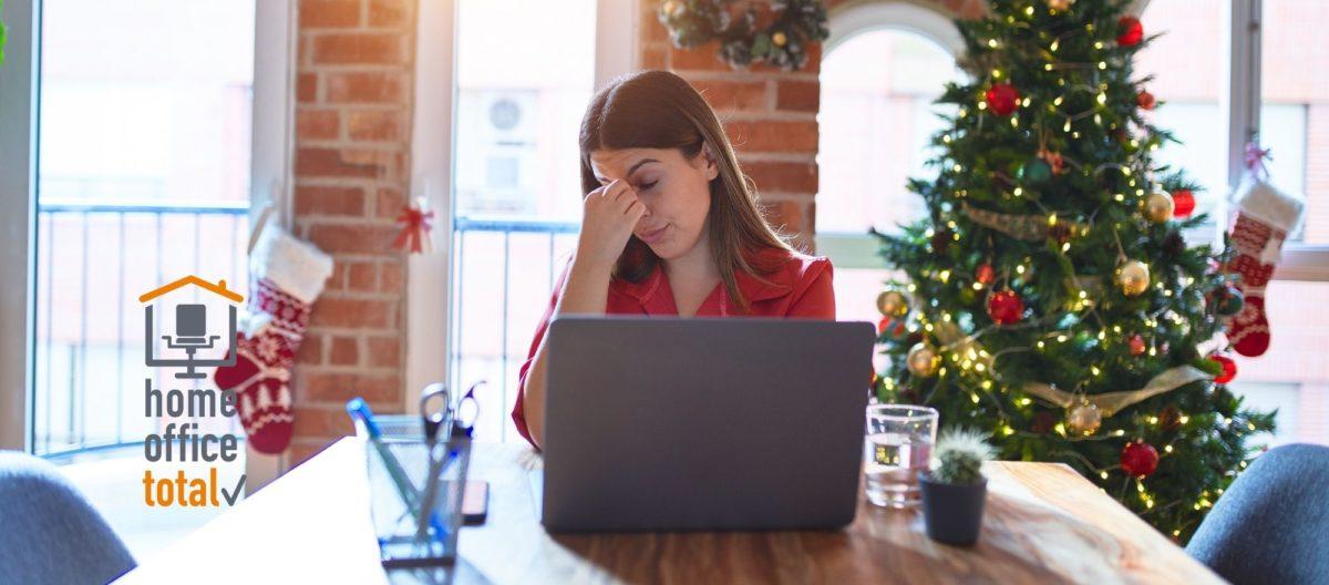 Frau an Esstisch mit Laptop und Weihnachtsbaum (Bild: Krakenimages.com/Shutterstock.com)